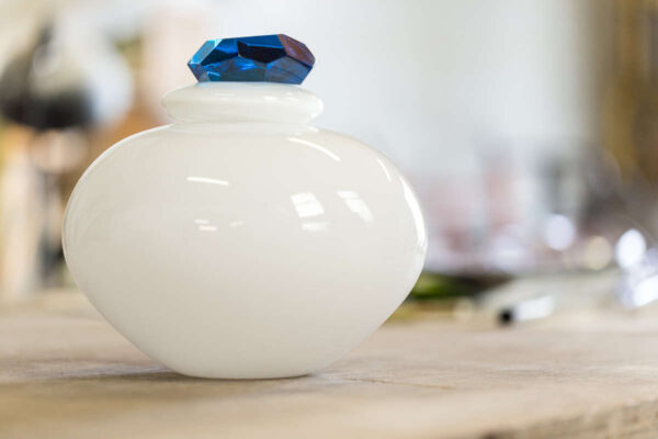 White glass urn with cut glass sapphire stopper. Hand blown and cut