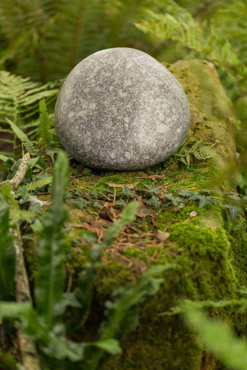Bronze pebble urn in forest